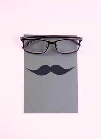 glasses and mustache on a delicate pink background. gift card for fathers day.