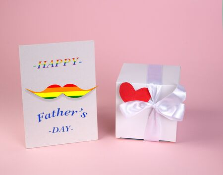 white gift box and card for fathers day. gentle pink background.