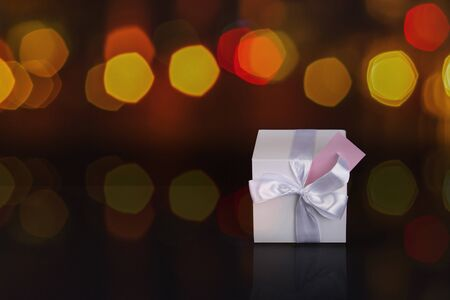 Gift box with bow and card. Blurred background.