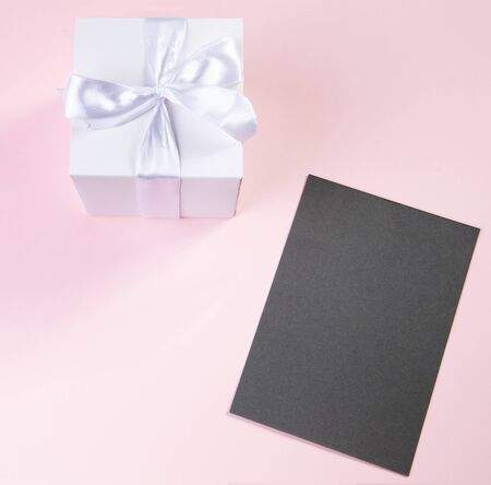 white gift box and greeting card for the holidays. delicate pink background.