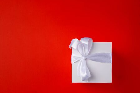 White Gift box on a red background. Space for text.