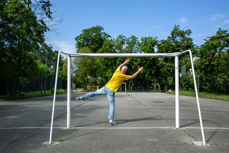 a gray-haired man catches an imaginary ball in a soccer goal