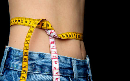 Slim female body in jeans. girl measures waist with centimeter. diet concept