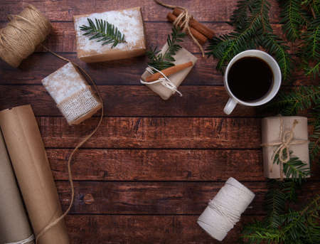 A cup of coffee stands on the table next to Christmas gifts Reklamní fotografie