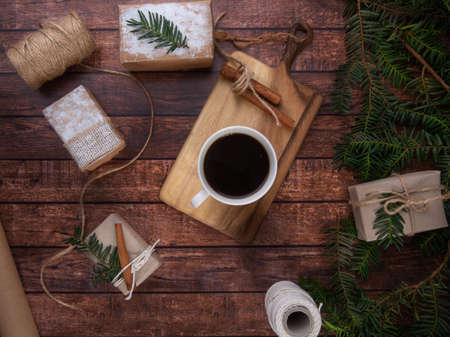 A cup of coffee stands on a dove on a wooden table Next to boxes with gifts