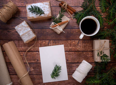 The postcard lies on a wooden table and there are Christmas gifts Reklamní fotografie