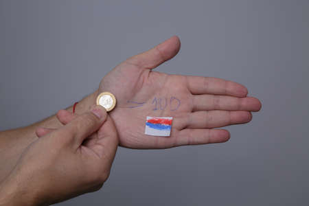 man hand holds euro coin and on the other palm course of 100 rubles is written
