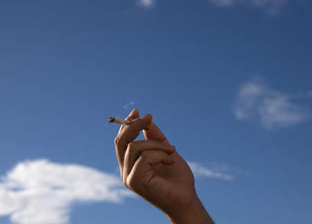 cigarette in a man hand against a blue sky. close up. Фото со стока