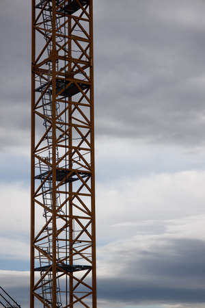 part of a construction crane against a blue sky with clouds, evening
