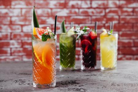 Quatre cocktails de fruits sur table.