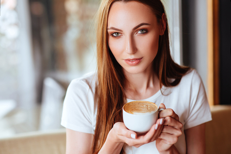 Girl in cafe with capuccino