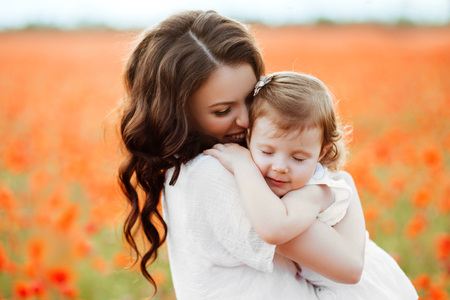 Beautiful mother and her daughter playing in spring flower field Stock Photo