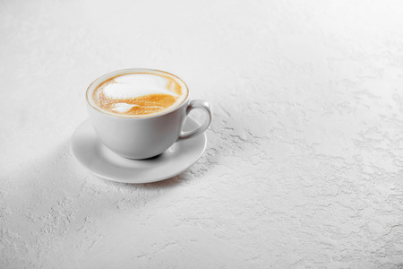 Cup of cappuccino coffee on white background