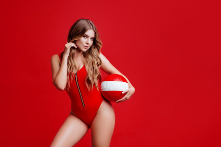 Pretty bikini model holding red ball in studio