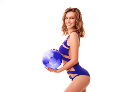 Pretty bikini model holding blue ball in studio