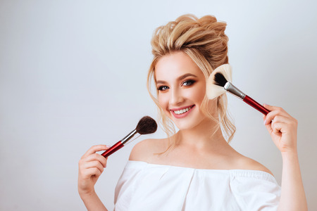portrait of happy smiling blonde woman with long wavy hair style holding brush. Banque d'images