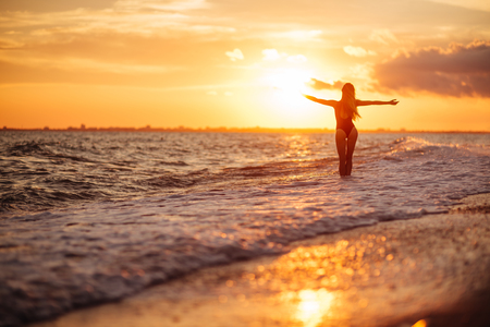 carefree woman dancing in the sunset on the beach.