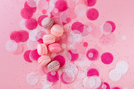 French macarons, confetti, and paper stars scattered on pink background