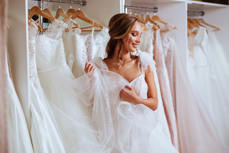 Bella novia está probando un elegante vestido de novia