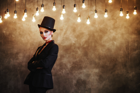 A girl in stylish top hat with skull make up. Halloween party.