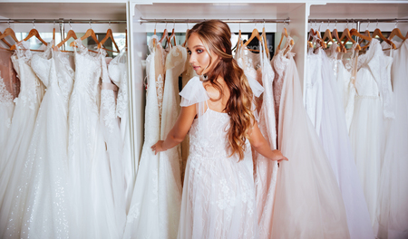 Attractive young bride is smiling while choosing wedding dress