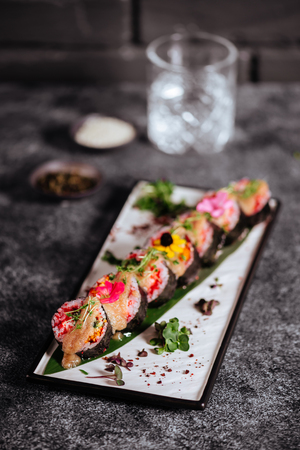 Various kinds of sushi served on black stone