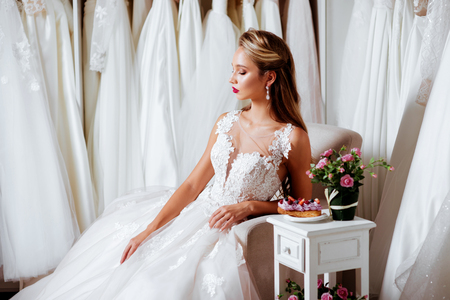 Back view of a young woman in wedding dress looking at bridal gowns Фото со стока
