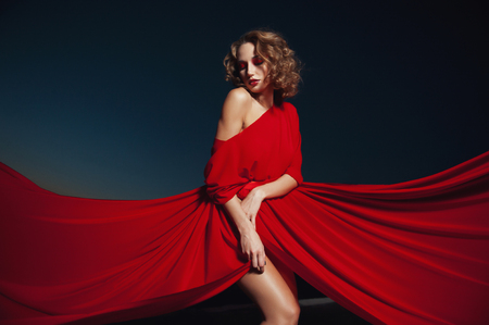 woman dancing in silk dress, artistic red blowing gown waving and flittering fabric Stock fotó
