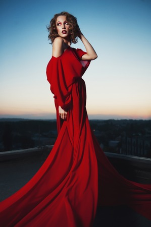 Fashion vogue style portrait of young stunning woman posing in red dress in sunset Imagens