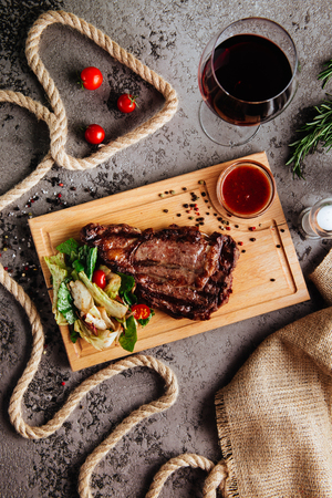 Grilled ribeye beef steak with red wine, herbs and spices on a dark stone background.