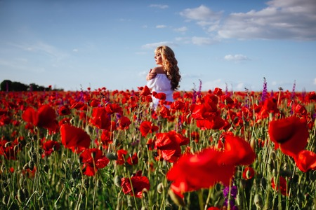 cheerful girl with curly blond hair in a huge poppy field alone Stock Photo