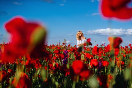 cheerful girl with curly blond hair in a huge poppy field alone, Stock Photo - 124680625