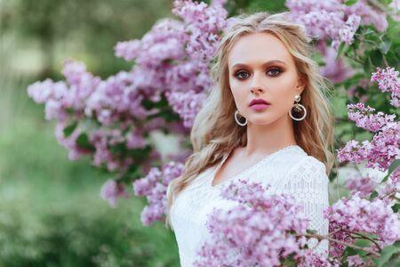 Mooie vrouw genieten van lila tuin, jonge vrouw met bloemen in groen park.