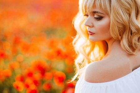 cheerful girl with curly blond hair in a huge poppy field alone, Stock Photo