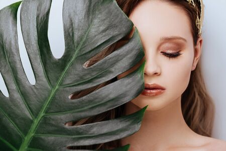 Portrait of young and beautiful woman in tropical leaves.