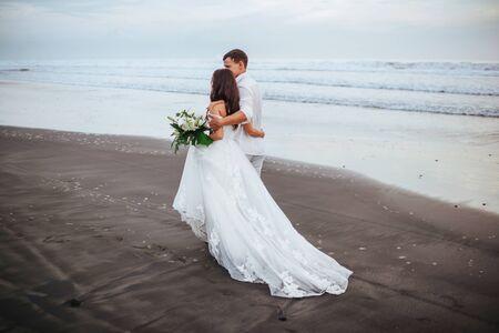 Elegant gorgeous bride and groom walking on ocean beach during sunset time. 写真素材