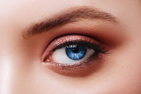 Close up view of blue woman eye with beautiful golden shades and black eyeliner makeup.