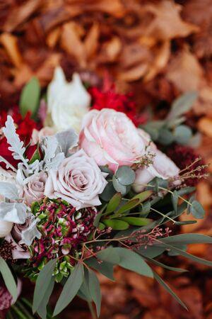 Bridal Wedding Bouquet on Autumn foliage background, outdoor