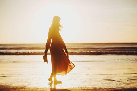 giovane bella donna magra sulla spiaggia al tramonto, giocosa, ballare, correre, vestito bohémien, stile indie, vacanze estive, soleggiato, divertirsi, umore positivo, romantico, spruzzi d'acqua, silhouette, felice