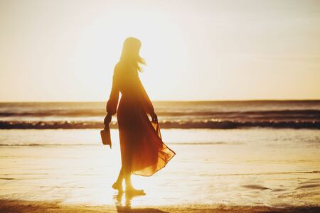 jeune belle femme mince sur la plage au coucher du soleil, ludique, dansant, courant, tenue bohème, style indie, vacances d'été, ensoleillé, s'amuser, humeur positive, romantique, éclaboussures d'eau, silhouette, heureux