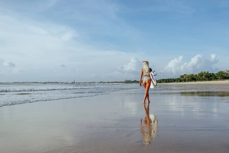 Surfer girl walking with board on the sandy beach.