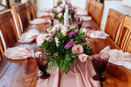 Vintage festive table setting with pink roses, candles and cutlery
