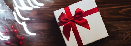 Banner of Christmas presents with red ribbon on dark wooden background in vintage style