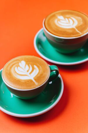 Cyan cappuccino coffee cups over orange background. Top view flat lay with copy space Foto de archivo