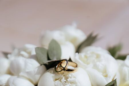 wedding rings lie on a beautiful bouquet Stock Photo