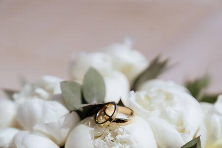 wedding rings lie on a beautiful bouquet Фото со стока