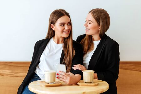 two young girls talking in a cafeteria Stock Photo