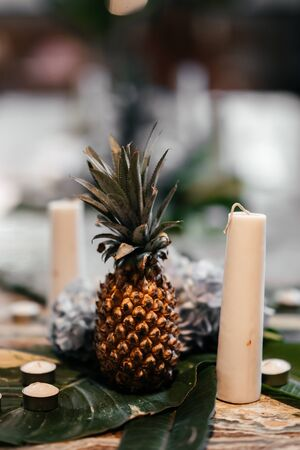 table in the boho style with pineapple candles plant decoration