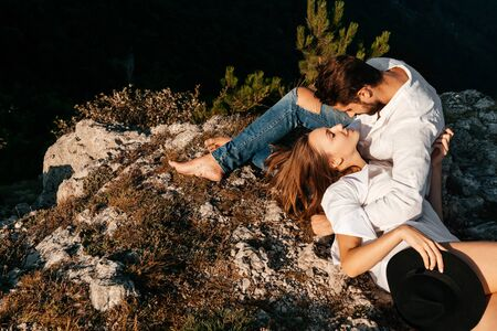 Attractive young loving couple of man and woman in the green mountain landscape