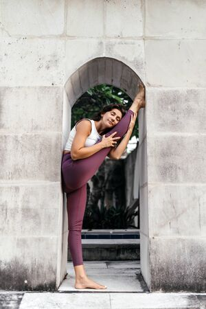 Woman practicing yoga performing yoga-asanas outdoors.